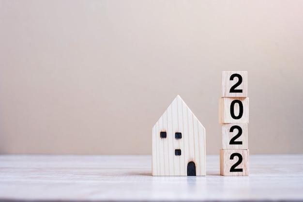 2022 felice anno nuovo con modello di casa su fondo di legno della tavola. concetti bancari, immobiliari, di investimento, finanziari, di risparmio e di risoluzione del nuovo anno