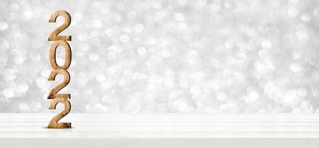 2022 felice anno nuovo su tavola di legno con parete bokeh argento scintillante