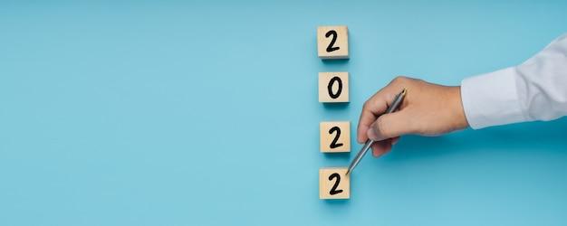 Numero del nuovo anno 2022 su blocco di legno con la mano che punta al piano con lo spazio della copia del banner di sfondo blu