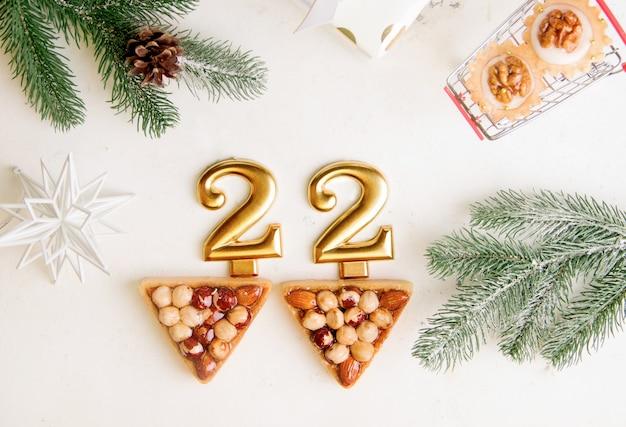 Numeri del nuovo anno 2022 su sfondo bianco accanto ai cookie