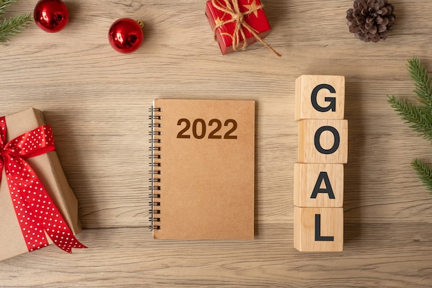 2022 capodanno con taccuino, regalo di natale e penna su tavola di legno. natale, felice anno nuovo, obiettivi, risoluzione, lista delle cose da fare, inizio, strategia e concetto di piano