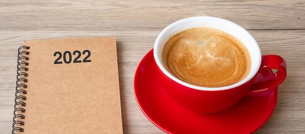 Taccuino 2022 e tazza di caffè sul tavolo di legno, vista dall'alto e spazio di copia. natale, felice anno nuovo, obiettivi, risoluzione, elenco delle cose da fare, concetto di strategia e piano
