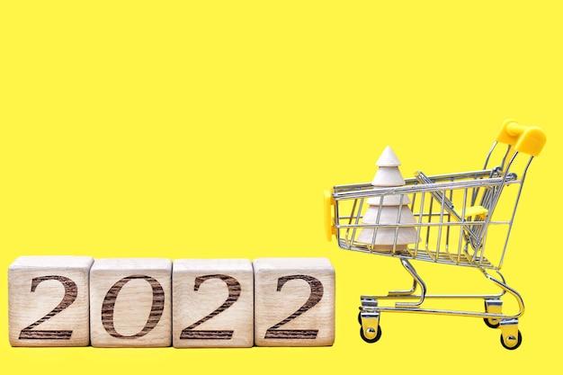 Numeri 2022 su blocchi di legno accanto a un carrello della spesa che trasporta un albero di natale in legno