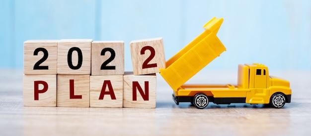 2022 pianifica blocchi cubici con un camion in miniatura o un veicolo da costruzione. nuovo inizio, visione, risoluzione, obiettivo, concetto industriale, magazzino e felice anno nuovo