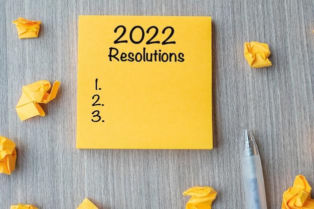 Risoluzioni 2022 parola su nota gialla con penna e carta sbriciolata su sfondo tavolo in legno. nuovo inizio, strategia e concetto di obiettivo