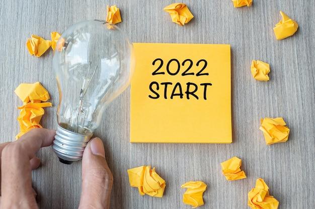 2022 inizia le parole sulla nota gialla e sulla carta sbriciolata con l'uomo d'affari che tiene la lampadina sul fondo della tavola di legno. anno nuovo nuova idea creativa, innovazione, immaginazione, risoluzione e concetto di obiettivo