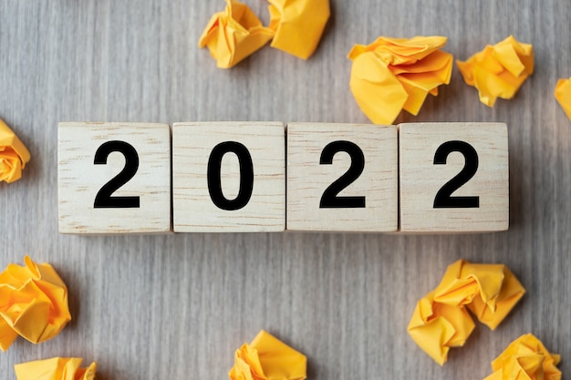 2022 testo cubo di legno e carta sbriciolata su sfondo tavolo in legno. anno nuovo nuove idee, creatività, innovazione, immaginazione, ispirazione, risoluzione, strategia e concetto di obiettivo