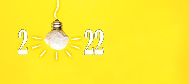 2022 lampadina di carta bianca su sfondo giallo, visione e risoluzione aziendale innovativa