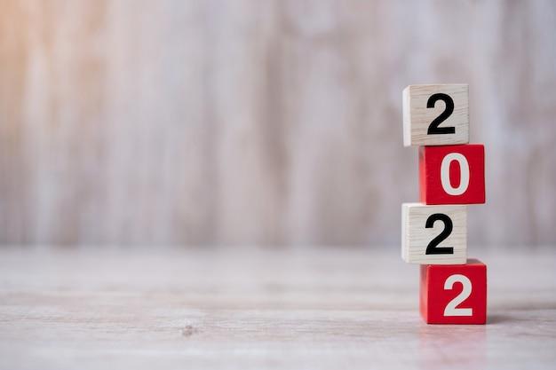 2022 blocco cubo di legno sullo sfondo della tabella. risoluzione, strategia, soluzione, obiettivo, affari e capodanno nuovo concetto di te e vacanza