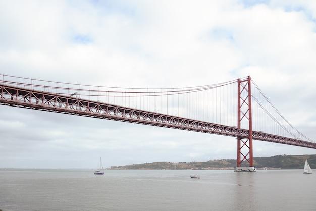 Ponte 25 aprile sul fiume tago sotto un cielo nuvoloso a lisbona, portogallo
