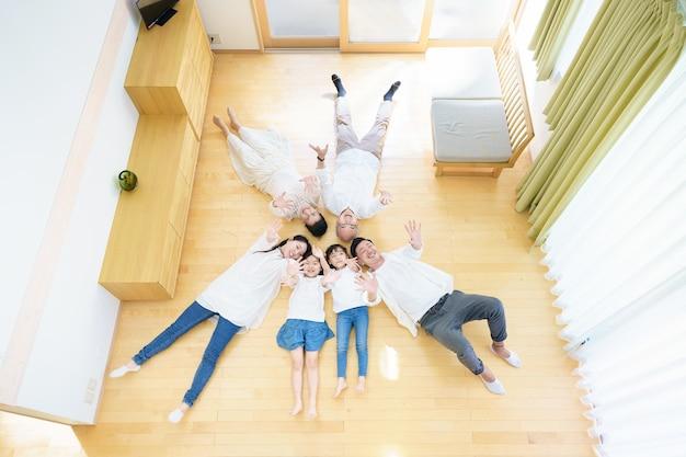 Famiglia di 3 generazioni sdraiata sul pavimento nella stanza
