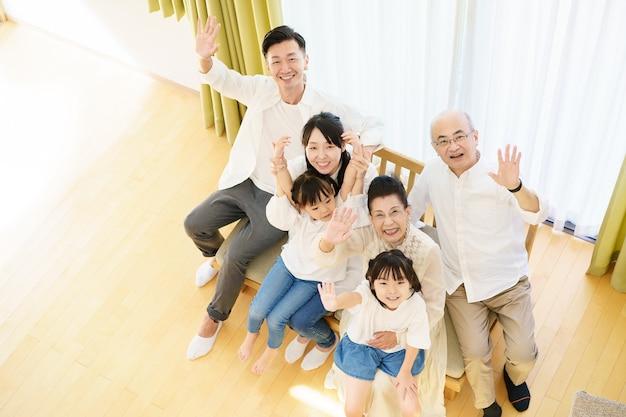 Famiglia di 3 generazioni seduta sul divano in camera
