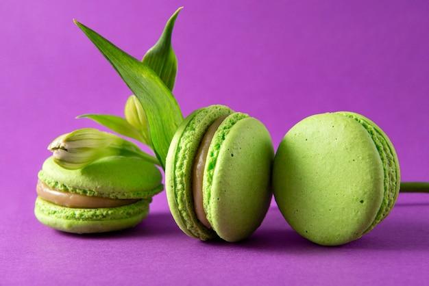 3 amaretti francesi verdi e un fiore su una superficie viola, biscotti francesi