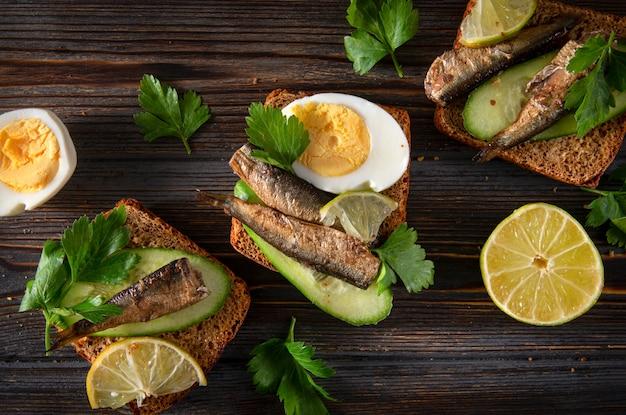 3 panini con spratti, prezzemolo, lime, cetriolo fresco, pane di segale e uovo sodo su una superficie di legno scuro, vista dall'alto, pesce in scatola,
