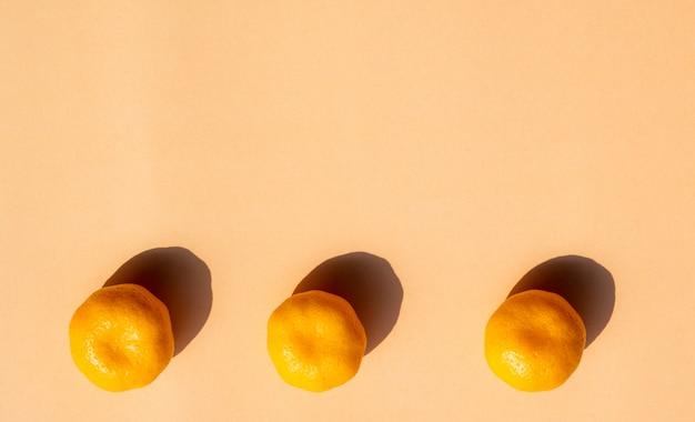 3 arance intere con forte ombra su sfondo arancione, copia spazio