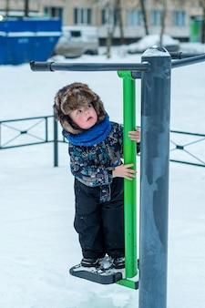Un bambino di 3 anni in tuta è in piedi su una macchina per esercizi all'aperto per adulti. passeggiata invernale.