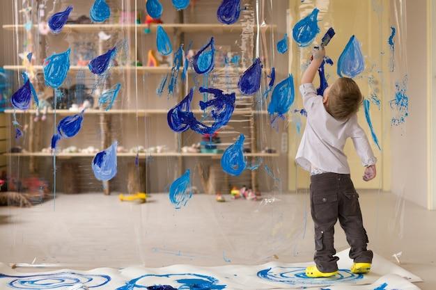 Bambino di 3 anni in camicia bianca disegna gocce di pioggia blu su materiale trasparente