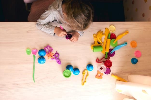3 anni ragazza arti creative. mani del bambino che giocano con la plastilina di argilla colorata. autoisolamento covid-19, formazione online, homeschooling. ragazza del bambino che studia a casa, apprendimento a casa