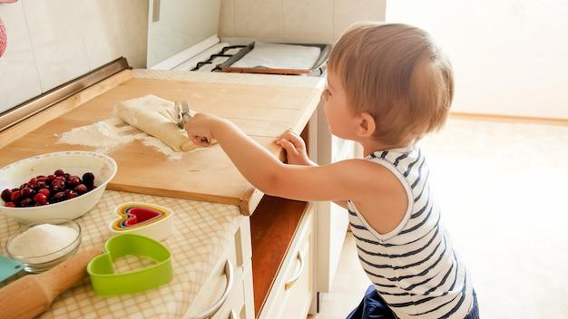 Bambino di 3 anni che arrotola la pasta su una tavola di legno e prepara i biscotti per la colazione