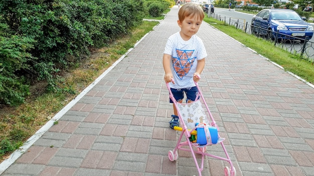 Ragazzo del bambino di 3 anni che cammina con la carrozzina del giocattolo sulla via. ragazzo che gioca con i giocattoli per le ragazze.