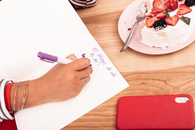 30 cose da fare. vista dall'alto di un taccuino sdraiato sul tavolo con una bella giovane donna che scrive