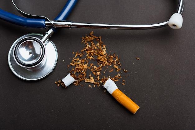 31 maggio della giornata mondiale senza tabacco non fumare close up di sigaretta mucchio rotto o tabacco e medico stetoscopio
