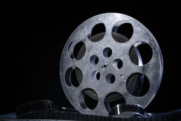 Bobina di pellicola da 35 mm con illuminazione drammatica su sfondo scuro