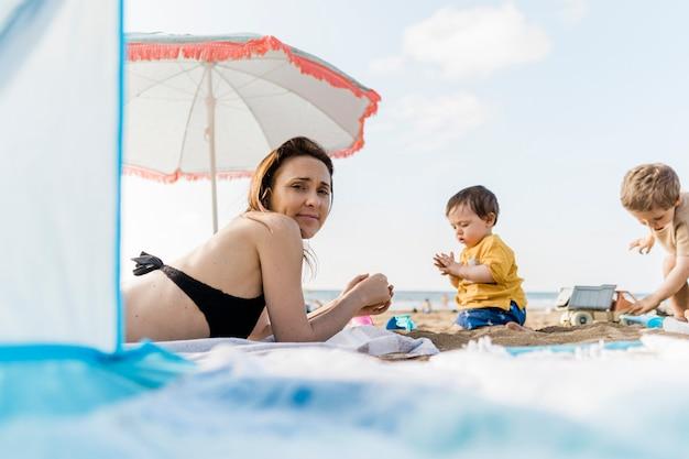 Madre millenaria di 35 anni in spiaggia in estate con i suoi due figli. madre single in vacanza concept