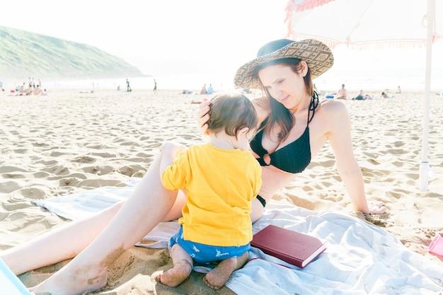Donna millenaria di 35 anni che si gode un pomeriggio soleggiato in spiaggia in estate o in primavera con suo figlio di un anno. madre single