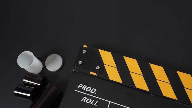 Pellicola per stampa a colori da 35 mm e clapperboard su sfondo nero