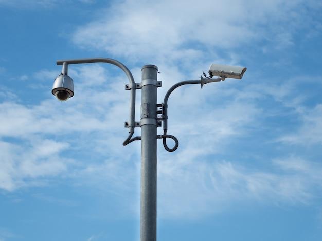 Il cctv della cupola dell'occhio di pesce di 360 gradi e la telecamera cctv sono installati sulla colonna contro il cielo blu.