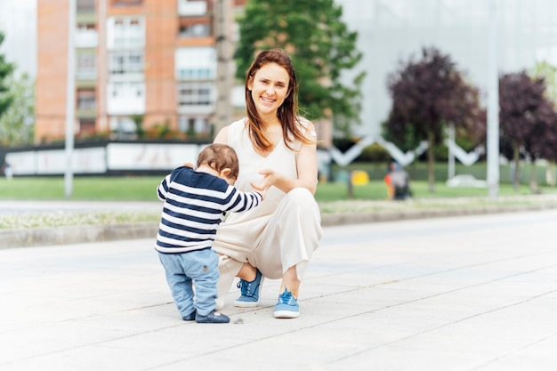 Madre di 37 anni con il suo bambino per strada che gli insegna a camminare