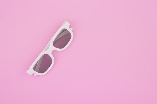 Gli occhiali 3d per guardare film in un cinema sono isolati su uno sfondo rosa pastello.
