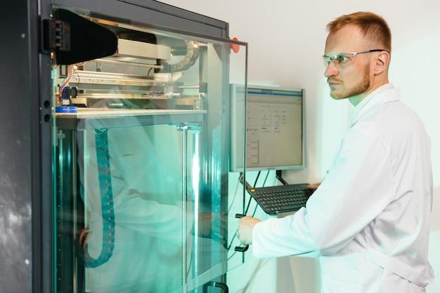 L'operatore maschio bello della stampante 3d lavora con la macchina di grandi dimensioni