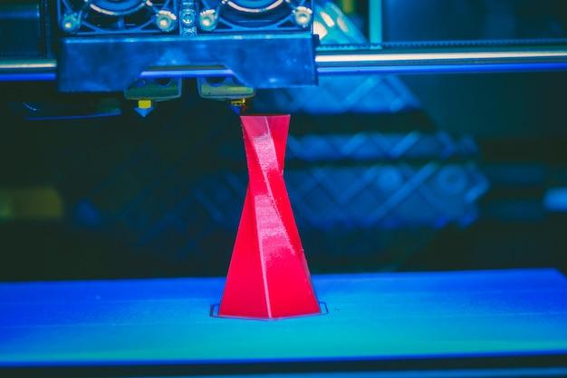 Stampante 3d che stampa un oggetto triangolare di volume isolato di colore rosso sulla base di un primo piano di sfondo blu e nero. moderna tecnologia di stampa 3d