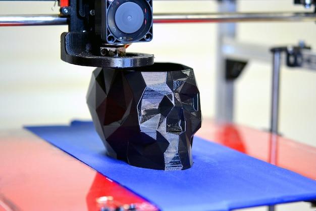 Stampante 3d che stampa un modello sotto forma di teschio nero in primo piano. la quarta rivoluzione industriale. il tridimensionale automatico esegue la modellazione plastica. tecnologia additiva moderna e progressiva