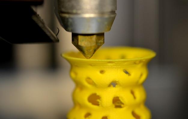 La stampante 3d stampa dal primo piano della figura di plastica. la stampante 3d fa il primo piano del modello giallo su una superficie piana grigia