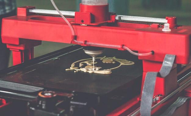 Stampante 3d che stampa un impasto liquido. stampante 3d frittelle con pasta liquida di diverse forme ravvicinate. moderne tecnologie additive 4.0 rivoluzione industriale