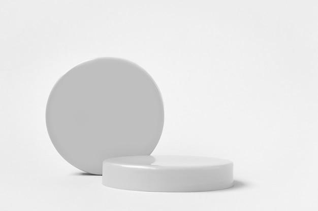3d rendono i piedistalli grigi e il podio del cerchio per il prodotto cosmetico su fondo bianco