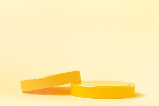 3d rendono i piedistalli gialli per i prodotti cosmetici su sfondo giallo