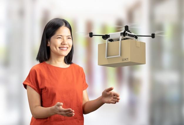 Il drone di consegna di rendering 3d invia una scatola di cartone a una donna asiatica