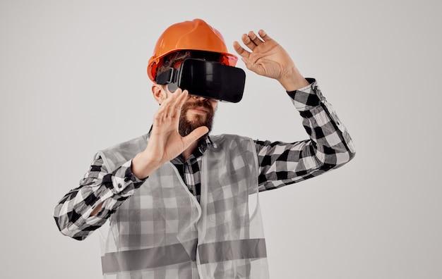 Uomo di cappello duro arancione di occhiali di realtà virtuale 3d nella costruzione di internet della camicia a quadri