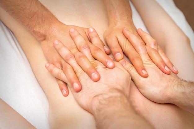 4 mani massaggiano la schiena del paziente. due massaggiatori che fanno il massaggio. avvicinamento