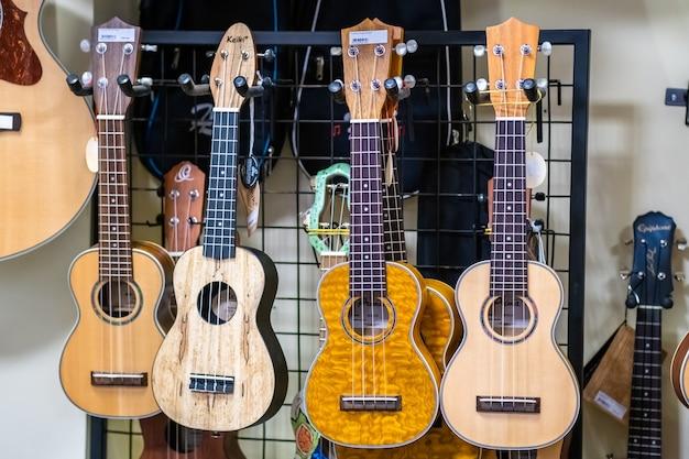 4 piccole chitarre acustiche tradizionali havaiane ukulele appese al negozio di musica