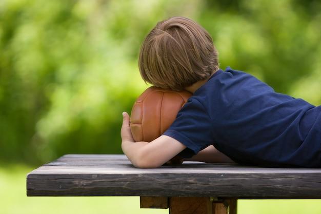 Bambino di 4 anni con una maglietta blu navy con una palla marrone nel parco in attesa della partita