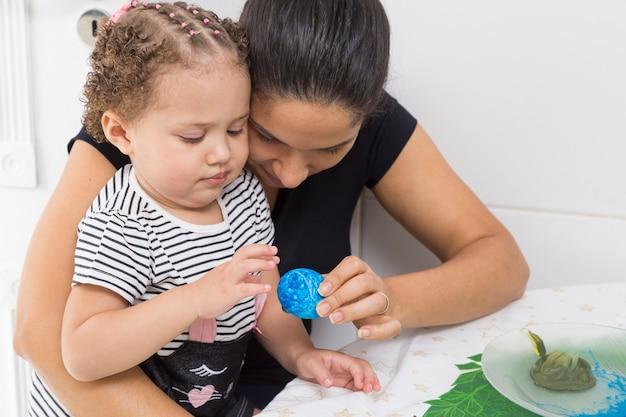 Donna di 40 anni che si siede con il bambino in grembo che tiene un uovo di pasqua blu.