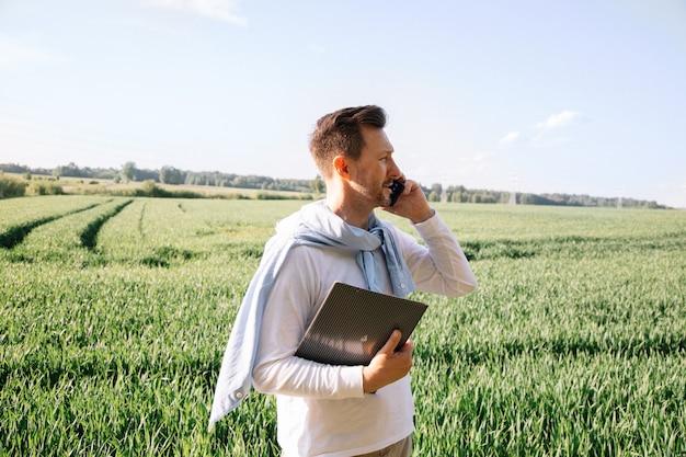 Un giovane agricoltore di 40 anni controlla il suo raccolto e negozia un accordo su uno smartphone