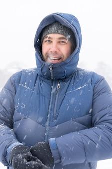 40c ritratto di uomo sorridente in abiti invernali in presenza di forti nevicate