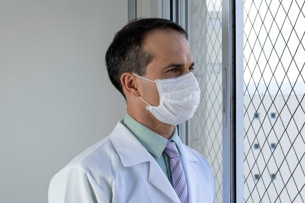 Medico di 44 anni con maschera camice bianco e cravatta guardando la finestra.
