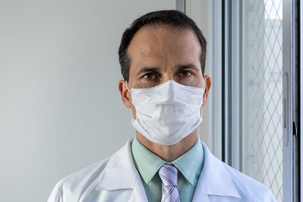 Medico di 44 anni con maschera camice bianco e cravatta.